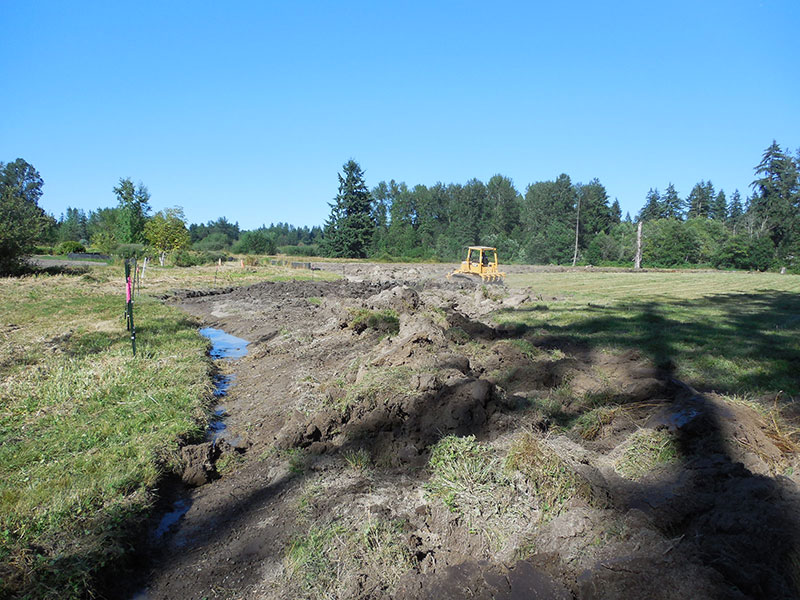 Plowing a strip of earth, to allow for the silt fence.